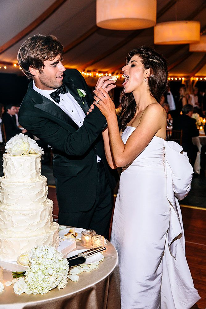 Groom feeds bride cake at their destination wedding reception at The Castle Hill…