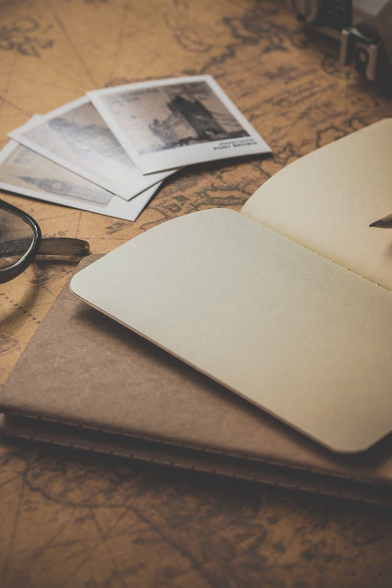 Free download of this photo: https://www.pexels.com/photo/black-frame-eyeglasses-beside-open-book-163034/ #notebook #table #travel