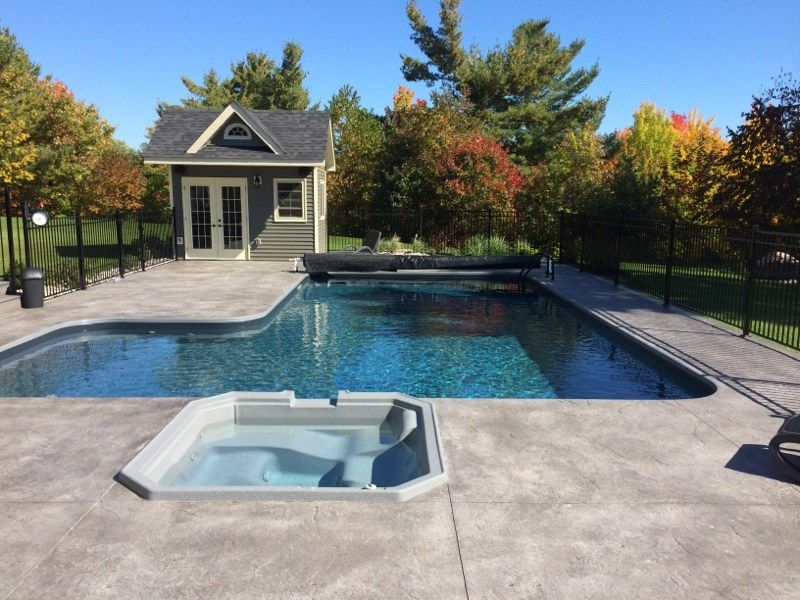 L Shaped Pool With Black Liner And Light Grey Stamped Concrete Including A Spillover Spa Concrete Swimming Pool Swimming Pool Decks Luxury Swimming Pools