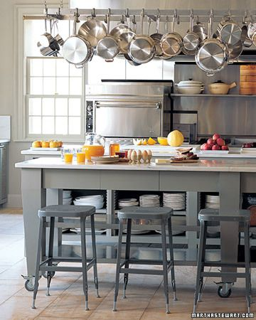 Islands offer seating and storage while an overhead steel rack keeps pots and pans reachable but out of the way.