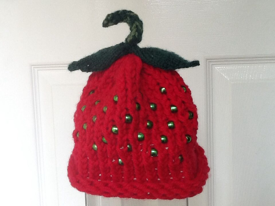 Strawberry hat. Loom knitted with green bead 'seeds', icord stalk and 3 needle knitted leaves. Pleased with this one.