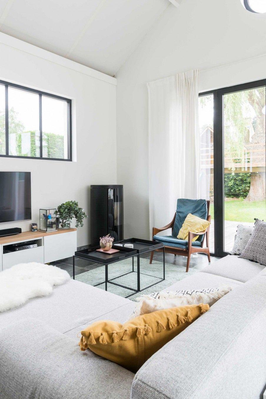 Woonkamer met grijze bank en zwarte tafeltjes | Living room with ...
