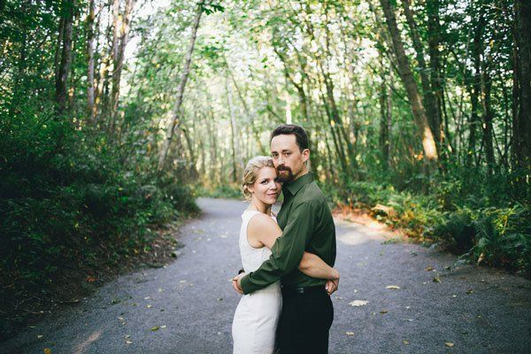 bride in simple white dress and groom in olive green shirt hug in woods after casual elopement @myweddingdotcom