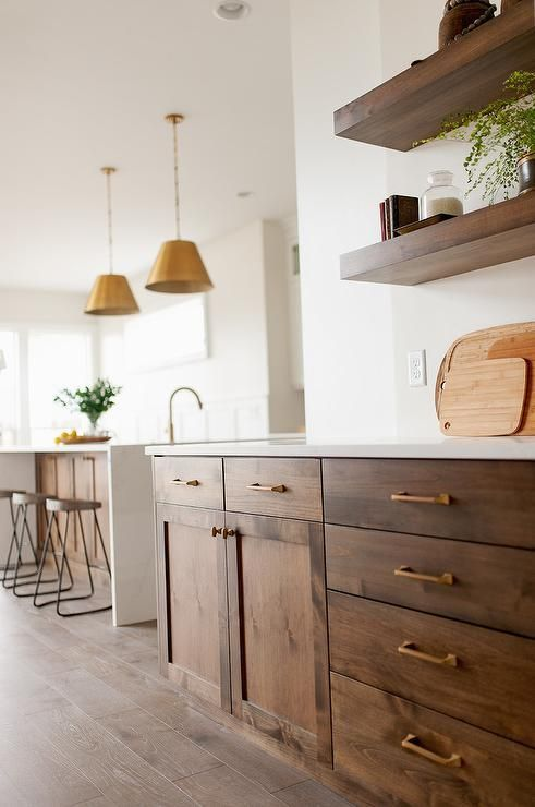 The beautiful brown oak shaker cabinets are embellished with brass rods and ...