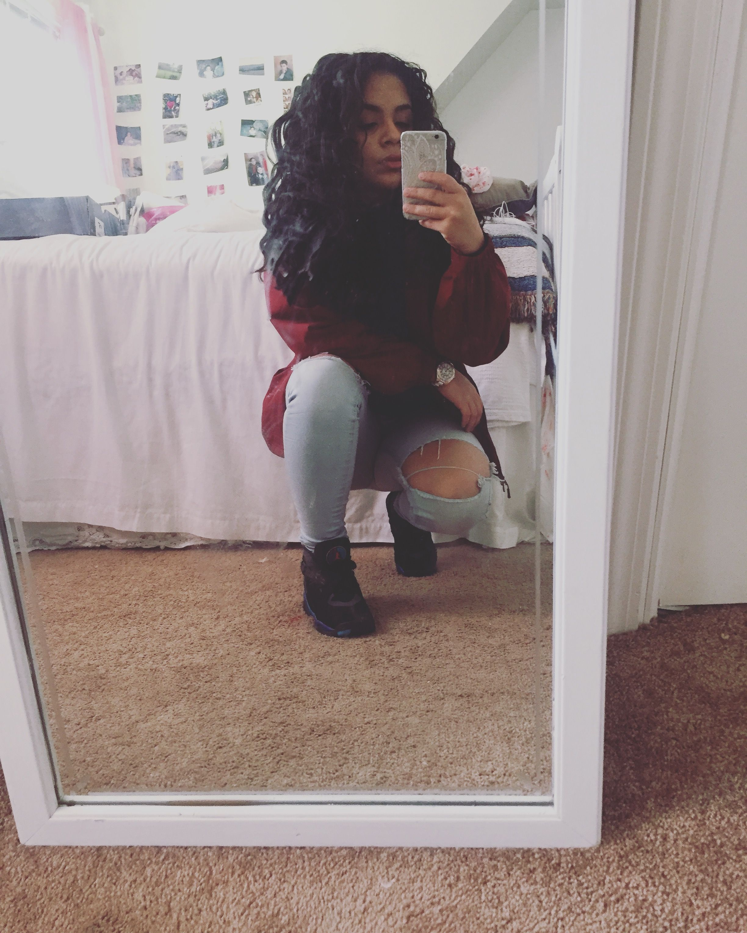 Urban style with ripped jeans, Jordan's, windbreaker, and black shirt. And curly hair