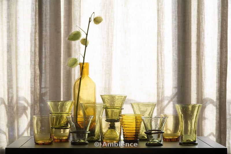 Riva Apartment. Collection of green and yellow vases on windowsill