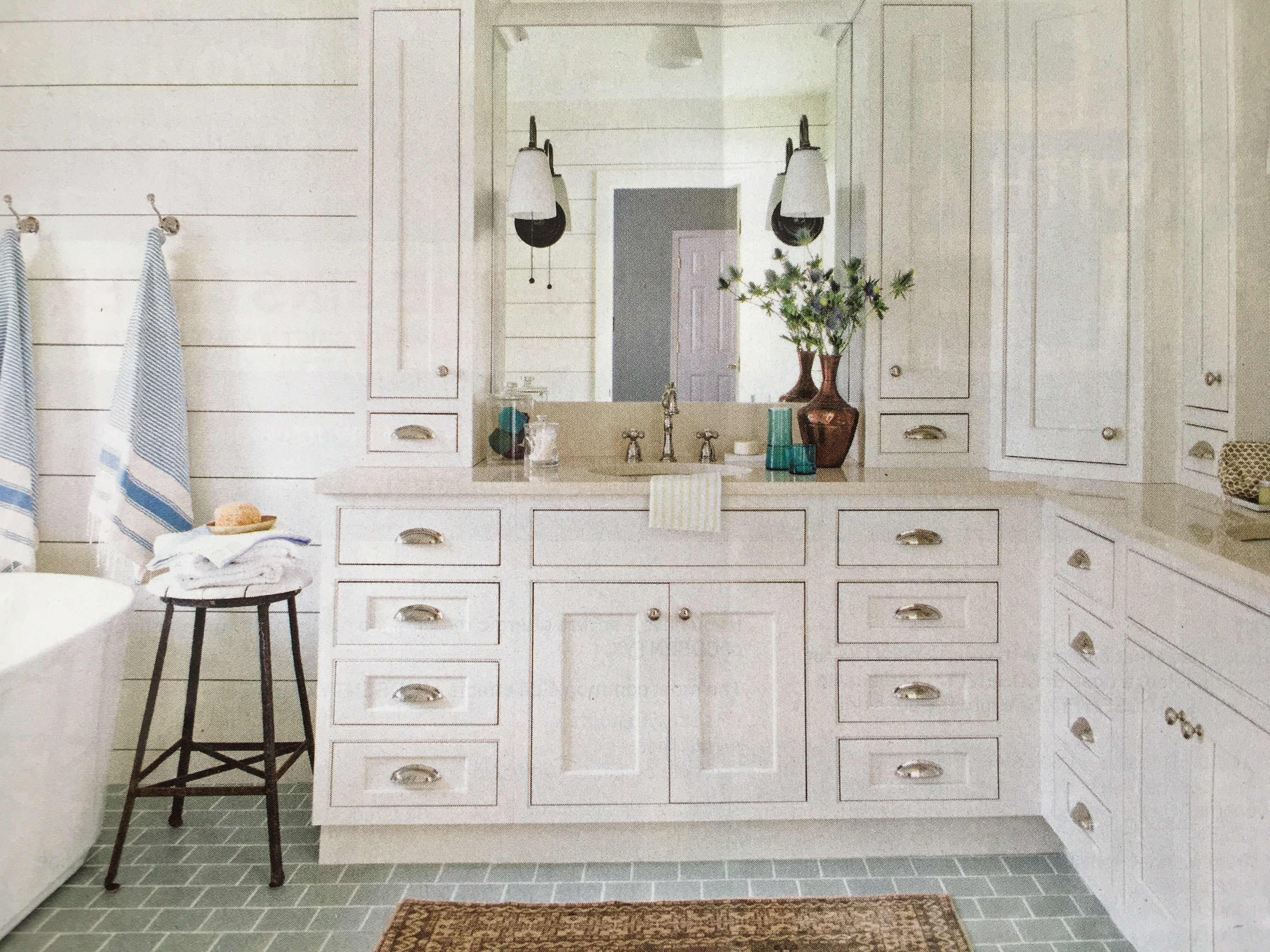 Sand color countertops, white wood cabinets, black iron fixtures and ...