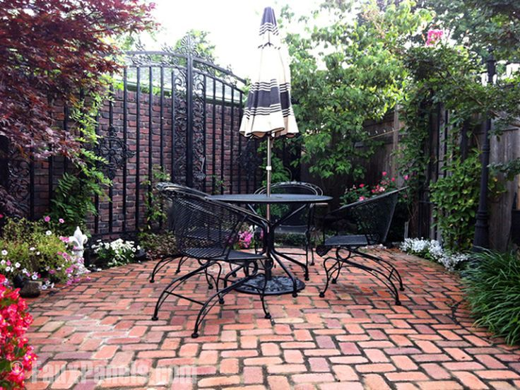Charming Enclosed Patio Garden Area Enhanced With Fake Antique Brick Panels Behind A  Wrought Iron Gate.