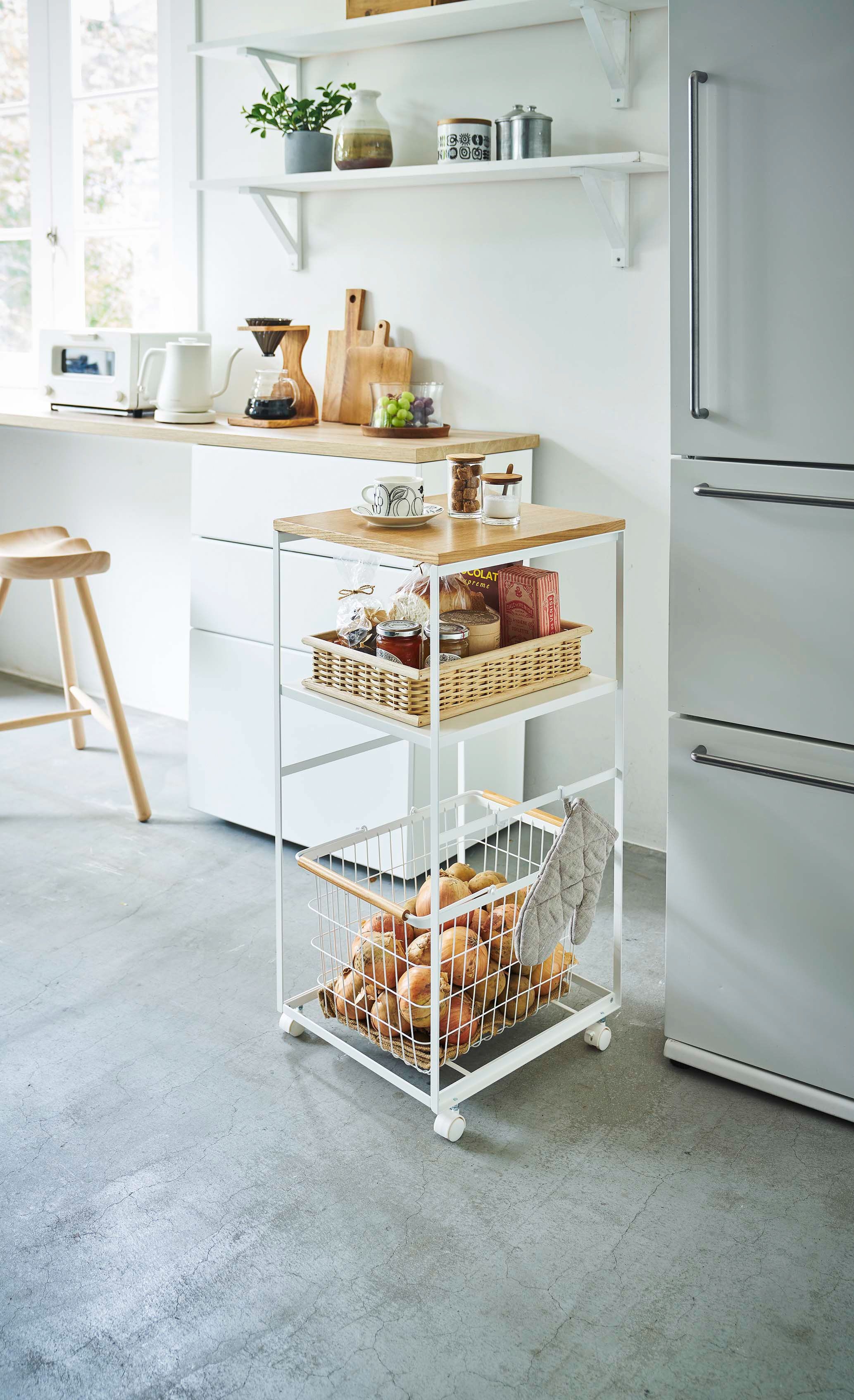 An extra table on wheels! This rolling kitchen cart boasts three levels of storage. Use the wooden tabletop as an appliance rack or breakfast bar. Bottom two levels add extra storage for spices, vegetables, or dried food storage. Use hooks for hanging utensils or pot holders. Roll it over to the dining table or around the kitchen with ease, then tuck it away when not in use. Cart and baskets sold separately.