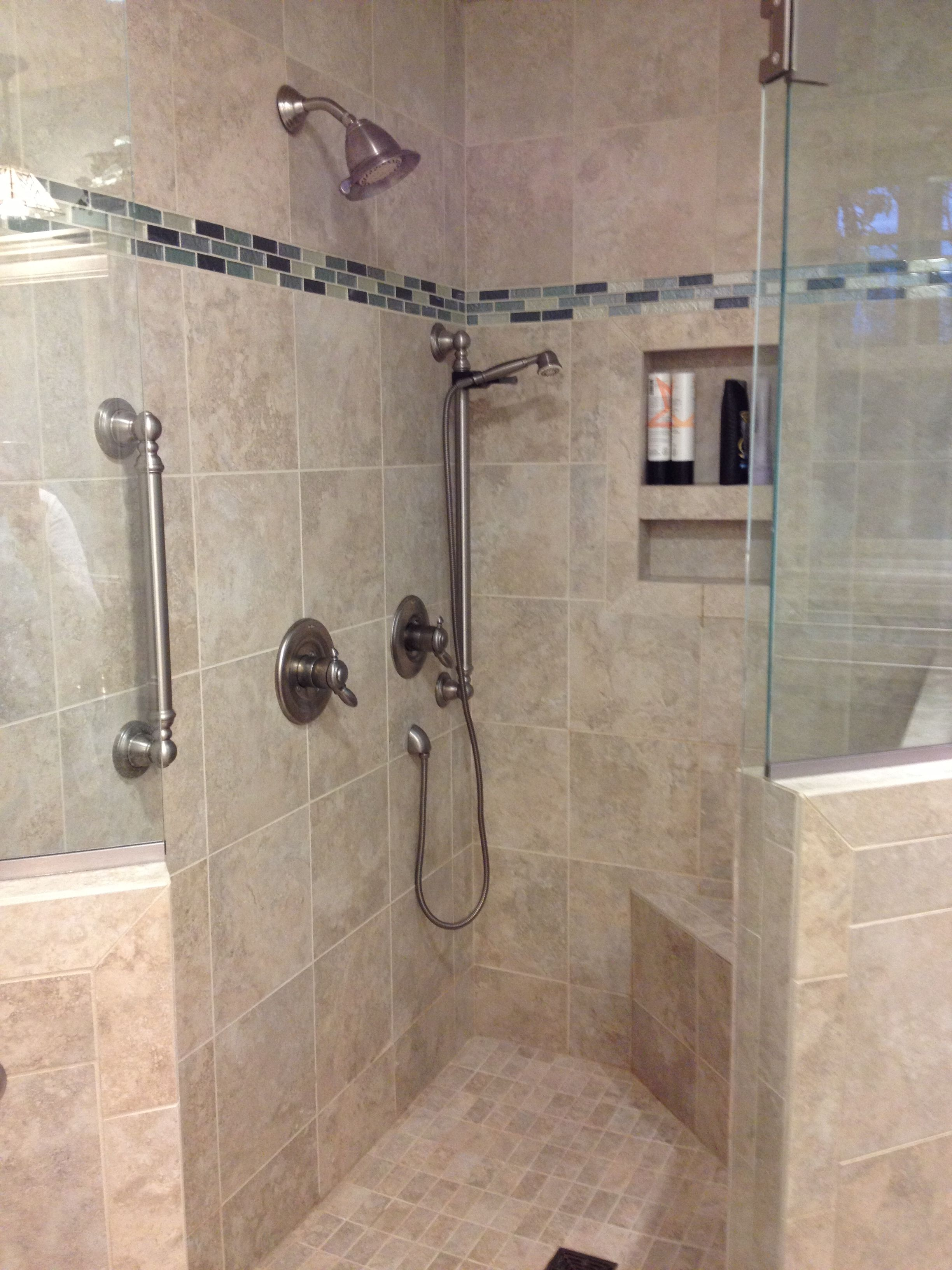 This custom tile shower has a built-in shower caddie, bench and hand ...