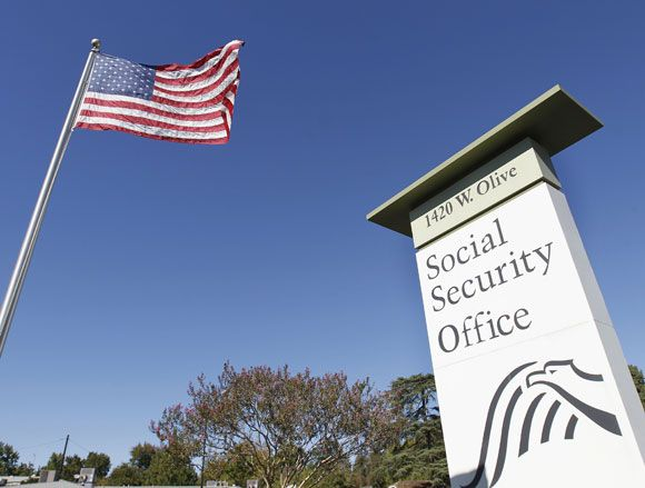 """Retirement-blog-flag-flutters-in-the-wind-next-to-a-social-security-office-sign (2)..!!! Social Security, as of August 1, 2014, will no longer allow people to get letters of verification, without signing up for a """" My Social Security"""" account, which would mean having access to a computer, and printer. If going to a library, etc, because of hot having one or the other, it could put pertinent personal information at risk, by using a public computer.!!!"""