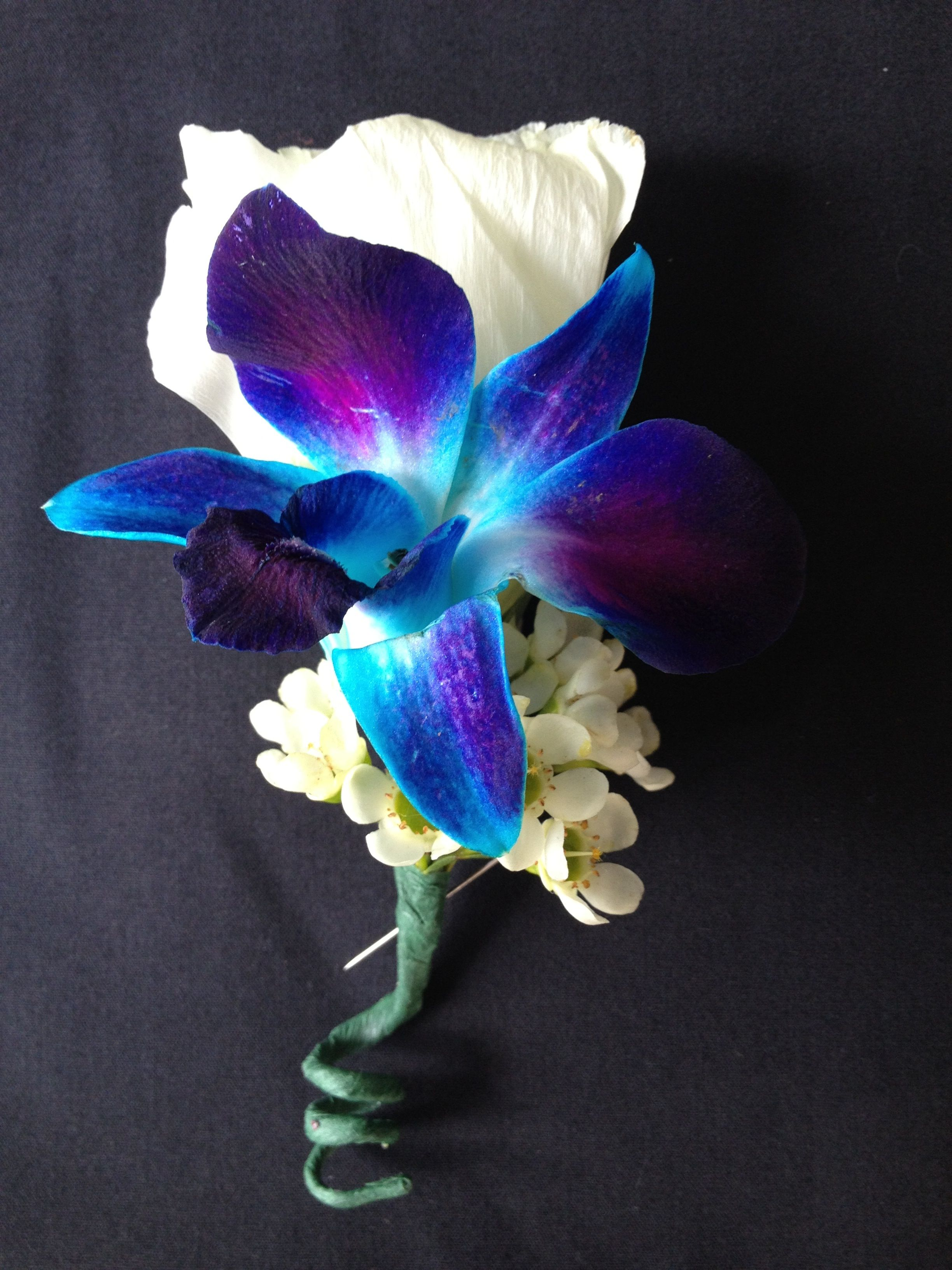 Boutonniere of white lisianthus and blue dendrobium orchid