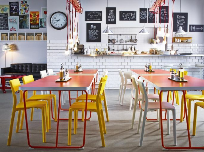 A Restaurant With Orange Tables Combined With Chairs In Yellow And White.