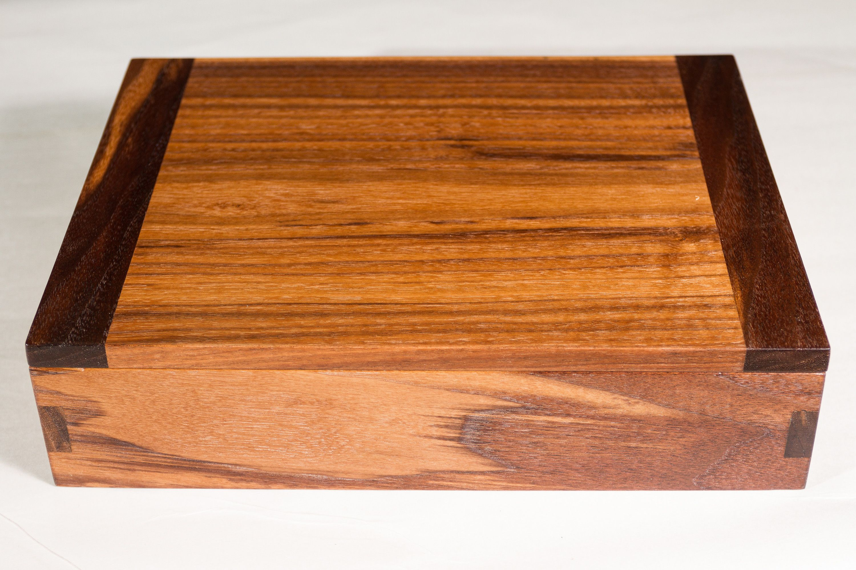Walnut box with breadboard ends on the lid and flush cut finger joints.