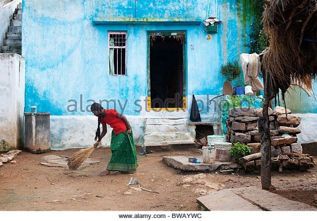 Young indian girl sweeping the front yard of her home in a rural indian village - Stock Image