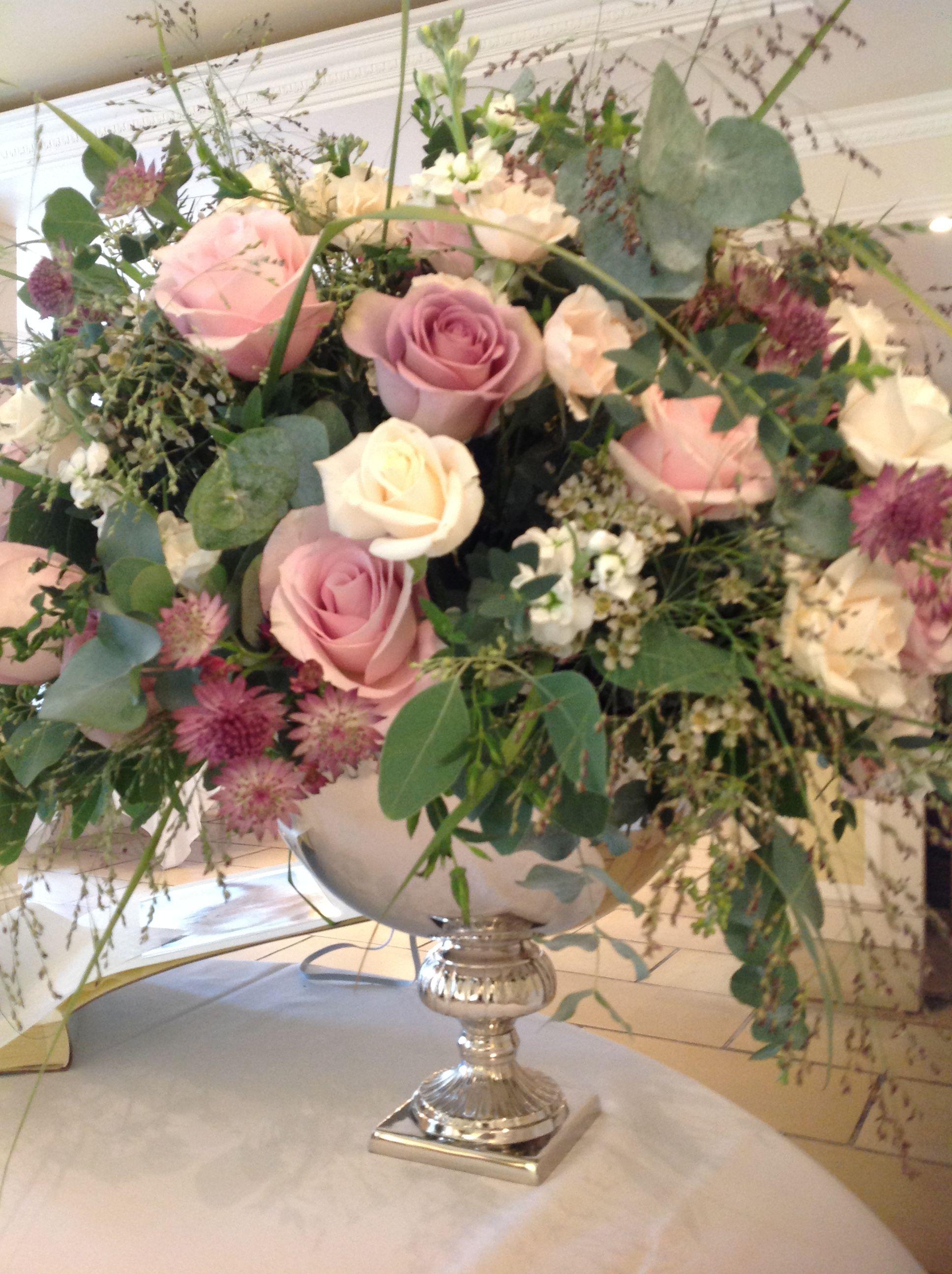 Pink roses and grey foliage in silver urn | Decoración de bodas ...