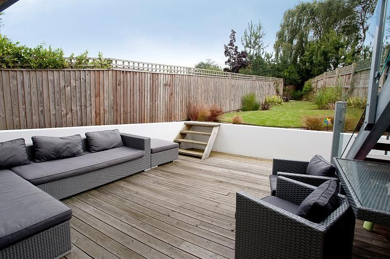 Photo of cool designer grey white walled decked garden odd for Garden decking ideas uk