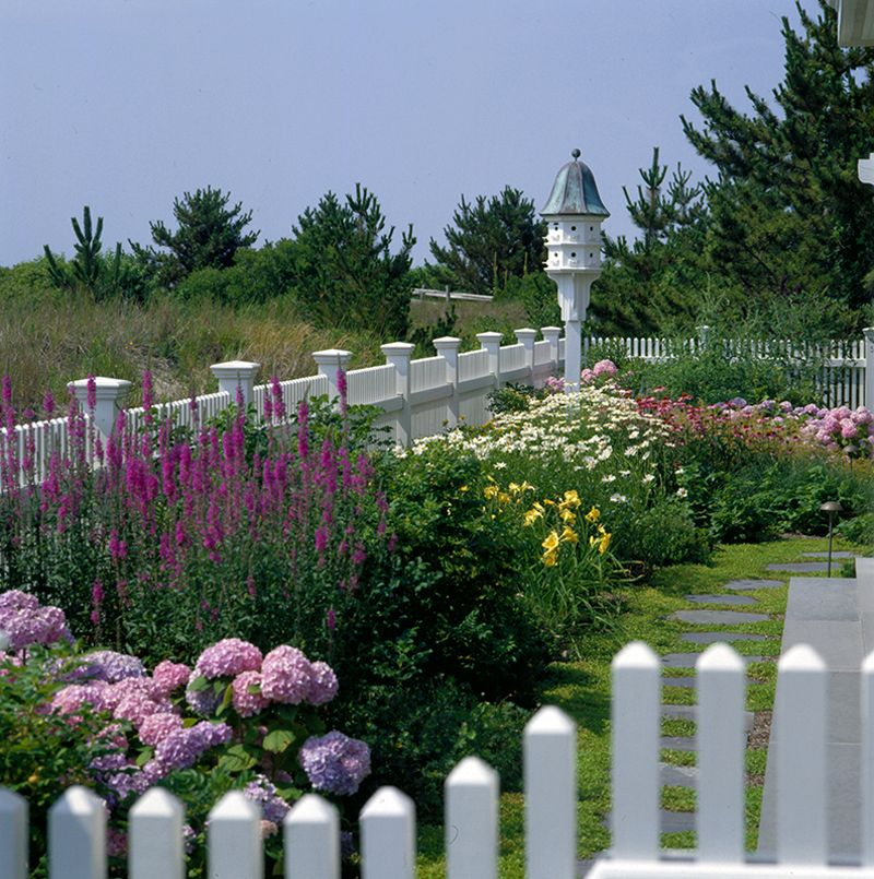 Birdhouse in a border of pink and lavender hydrangeas for Little flower garden ideas