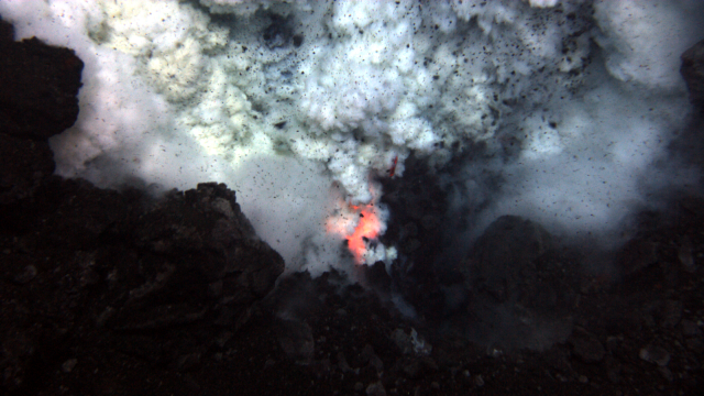 Explosion near summit of West Mata volcano throws ash and rock. Molten lava glows below.