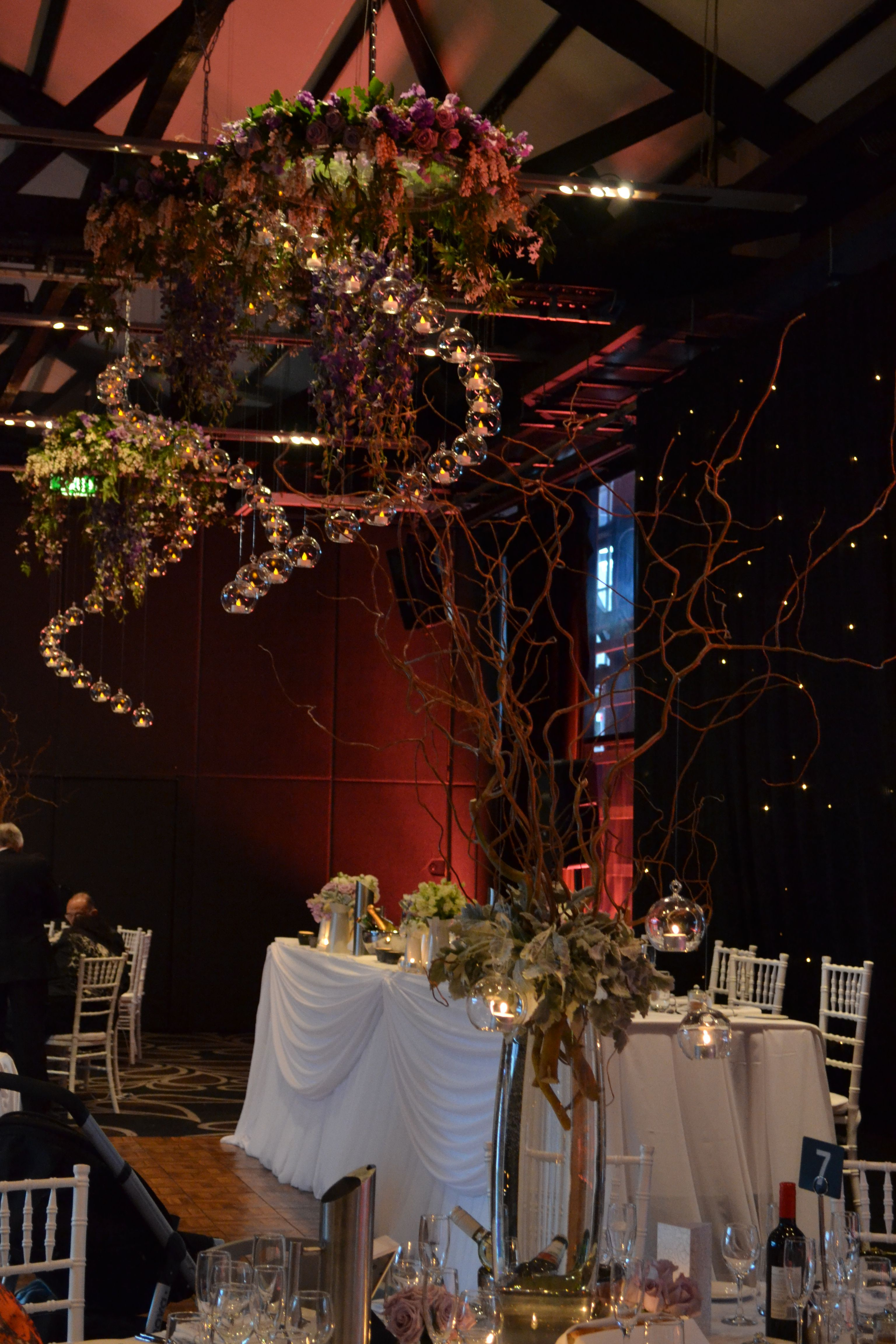 Hanging spiral chandelier with mauve floral garlands. Styled by Greenstone Events.