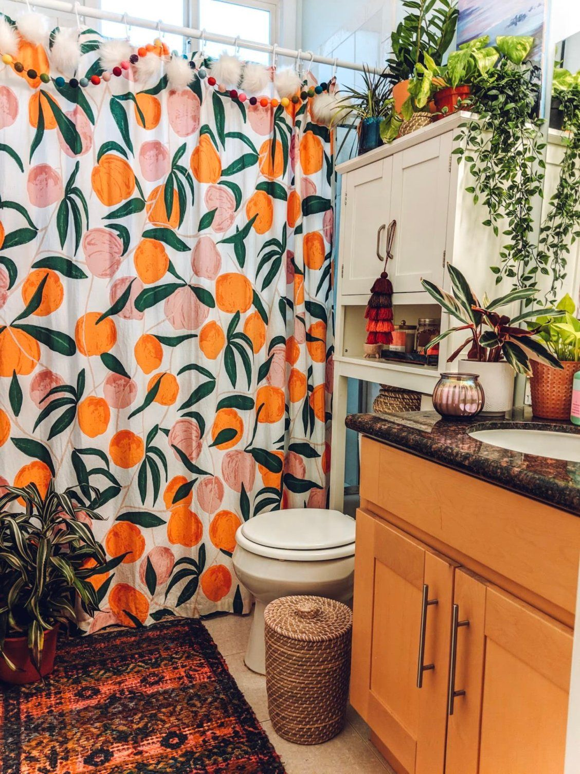 This boho bathroom shows how to add loads of color and personality to a standard rental. | House Tours by Apartment Therapy #maximalist  #bohemian, #eclectic, #colorfuldecor #bathroomideas #showercurtain #rentalbathroom