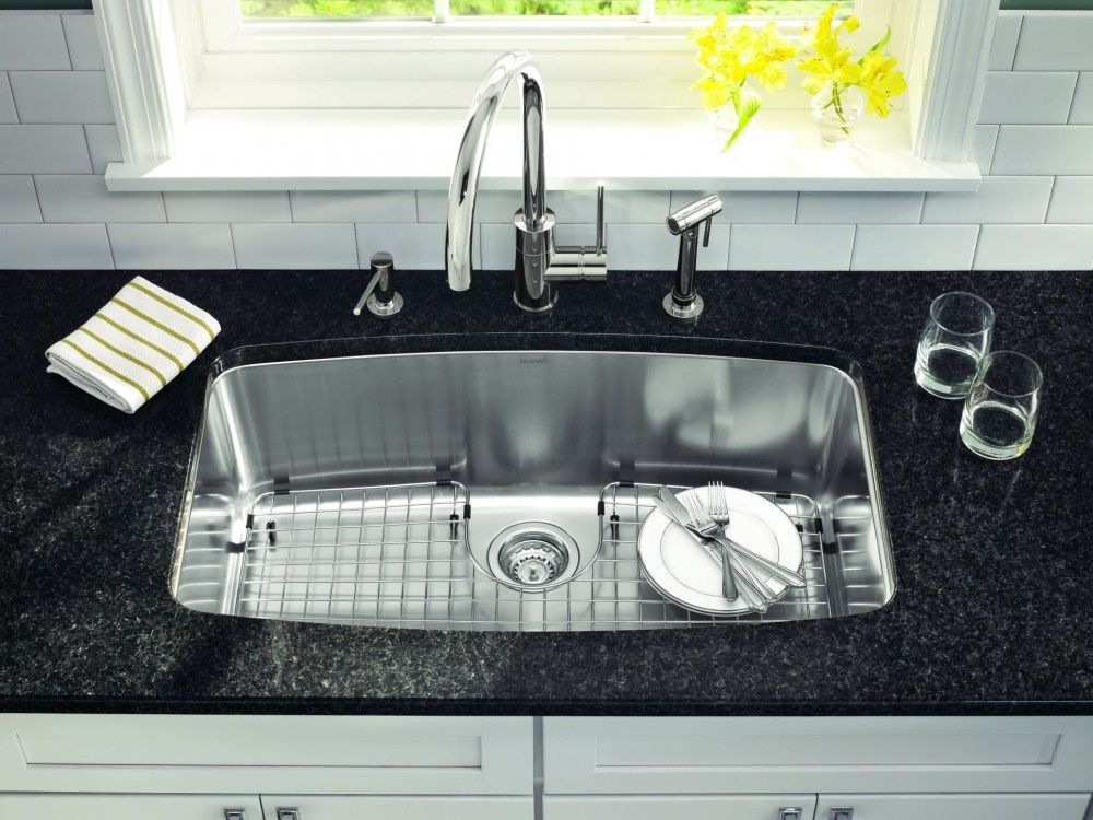 Undermount Stainless Steel Kitchen Sink With A Black Counter And