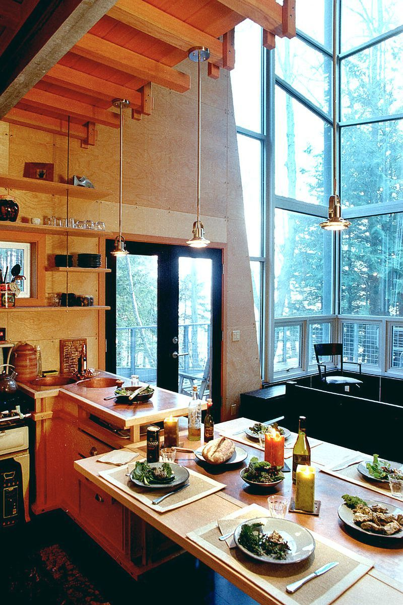 This elevated cabin features a double-height corner window. It has ...