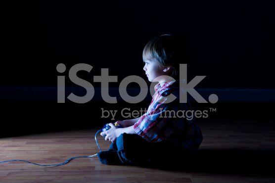 Boy plays video games in a dark room