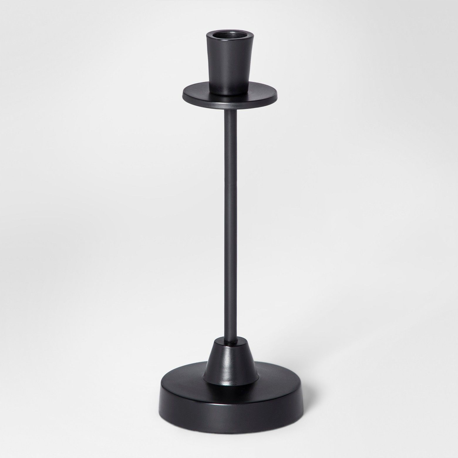A modern aesthetic is easy to incorporate into your home with this Taper Candle Holder from Project 62™. This sleek candle holder, with its matte black tone, adds a bold pop with minimalist design that will look great wherever you put it. Cluster several of these short candle holders together —either holding candles in a complementing color to your decor or empty as decorative pieces in their own right — for a beautiful modern design touch. <br><...