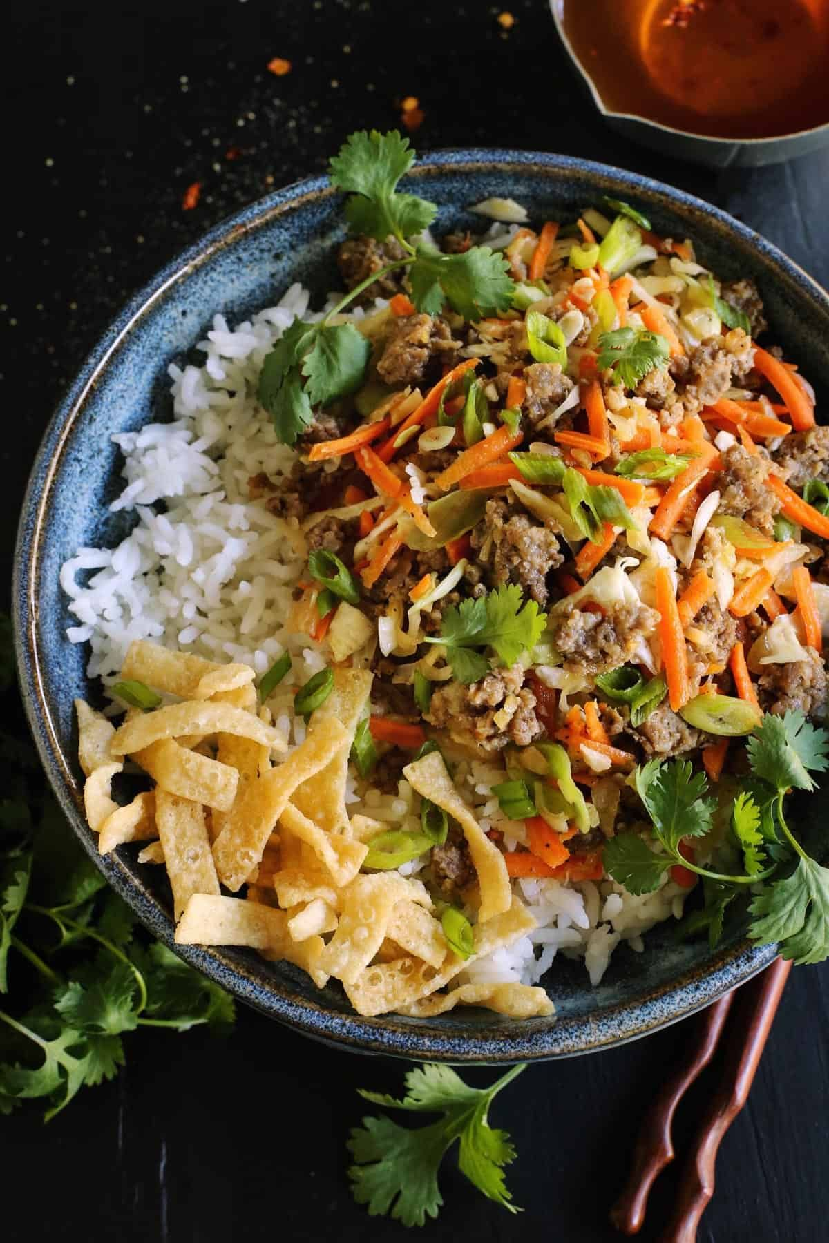 Egg Roll in a Bowl recipe from  An easy dish featuring egg roll flavors of ground pork cabbage and carrots Served with crispy wonton strips and a tasty Asian sauce
