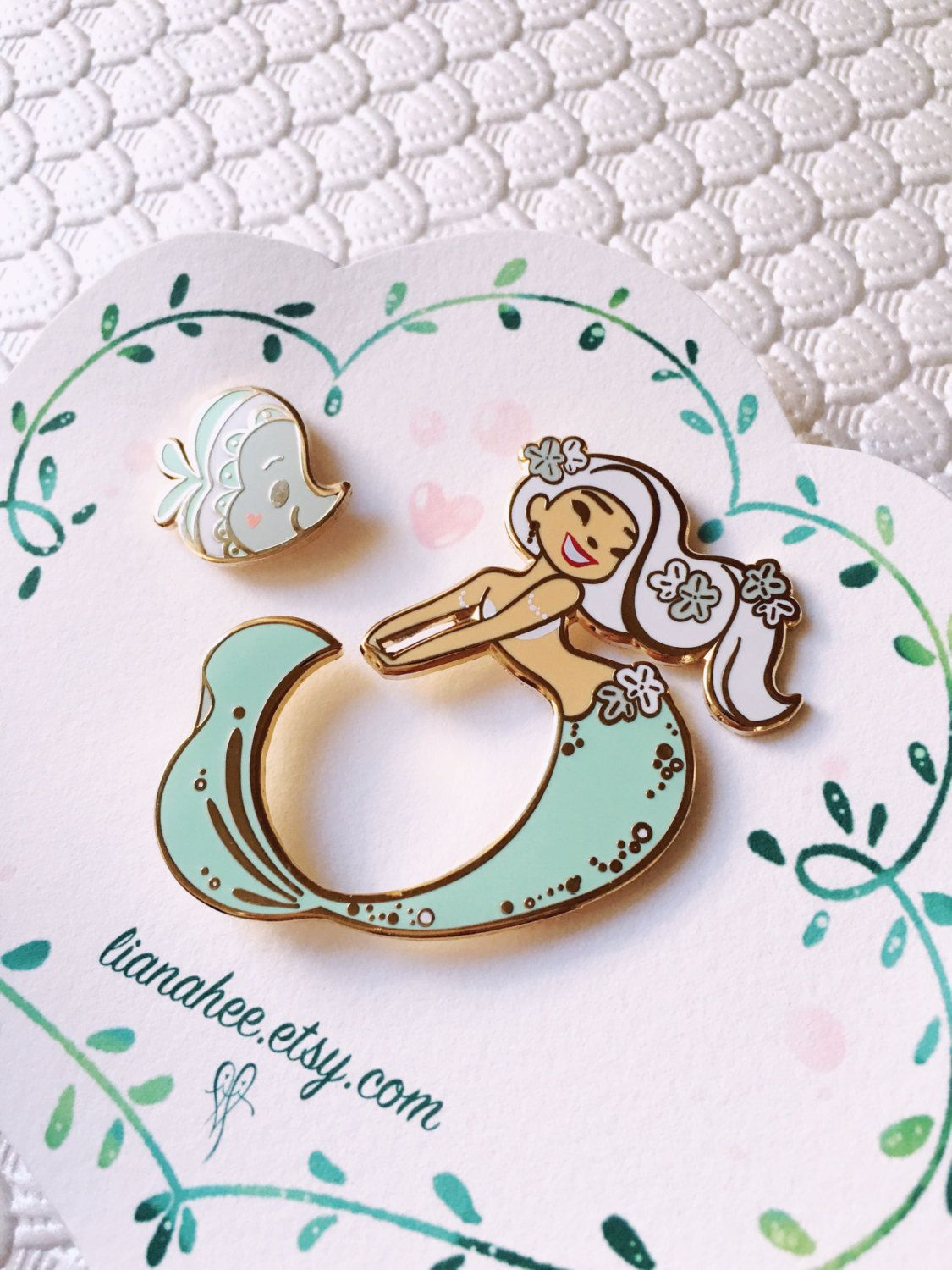 This mint mermie and her fishie friend is ready to play! Lovely gold toned enamel pins are a perfect addition to a bag or coat to stand out in the crowd. :) Mini mermie measures 2 inches tall and mini fishie measures .75 inches tall. Comes shipped with velvet paper backing inside a clear, protective, plastic sleeve.