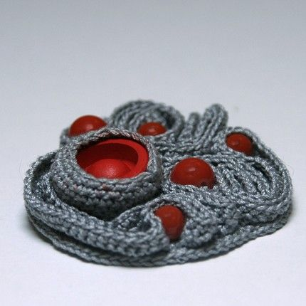 Cute, small grey crochet brooch with red button and red beads (my purchase from etsy-seller: http:\/\/OdetteDesigns.etsy.com) , complex laced labyrinth patterns and Brooch bar on the back.    Material: 100% mercerized cotton.  Measures: 2\/ 5cm diameter.    Cheer up your clothes with this pretty corsage.