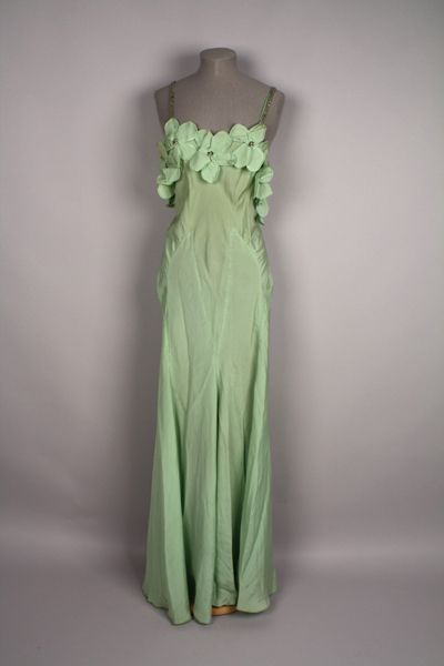 """1931-1936 pale green rayon evening dress featuring shoulder straps of double lines of rhinestones attached to the upper bodice. The bodice is cut deeply in back, and has a short, bound opening fastened with three snaps and one hook & eye closure. Top of the bodice in both the front and back features appliqued flowers with overlapping """"petals"""" of the same green fabric."""