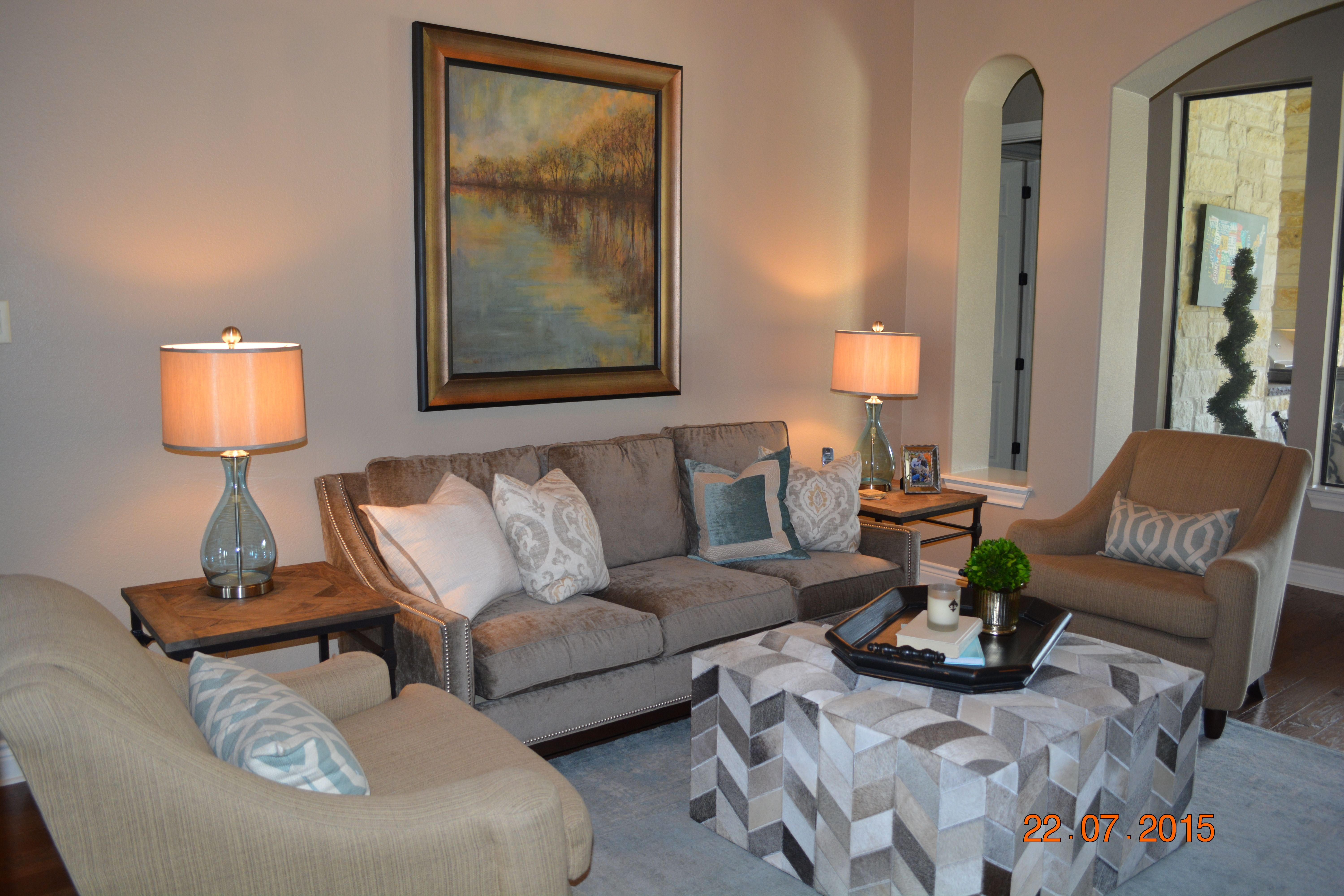 Four cowhide ottomans from Surya make the perfect coffee table for this room.  The turquoise rug, lamps and throw pillows accent the art.  This is the Giles sofa from Taylor King.
