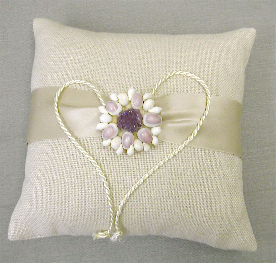 """Beach Ring Bearer Pillow.Perfect for a beach-themed wedding.  This beautiful pillow is made with sand-colored cotton fabric and finished with a wide satin sash.  The centerpiece is a fabric covered button adorned with real seashells and a gorgeous piece of amethyst druzy.Beachy and stylish!Approximately 8"""" square. $55.00"""