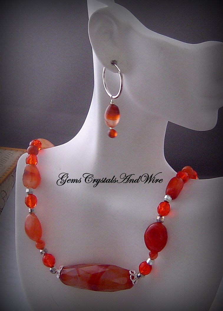 A gorgeous Carnelian focal is nestled between Sterling Silver and enhanced with more Carnelian and Swarovski Crystal ! This necklace is 19-1/2 inches long with a sterling spring clasp. An extension chain can be added upon request. As my gift to you- a pair of earrings ! Sterling Silver Hoops wi...