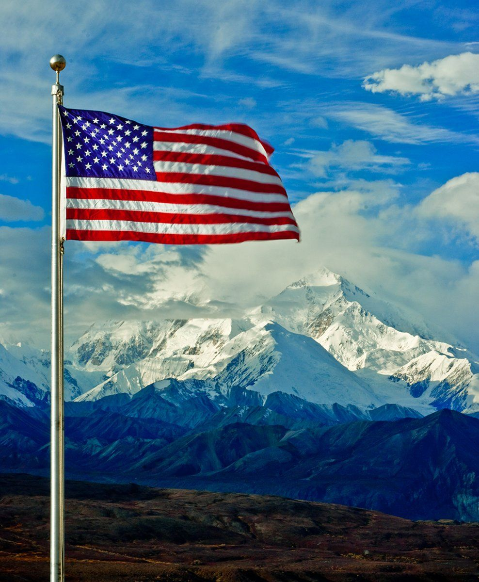 An American Flag On A Metal Flag Pole Waves In The Wind With A Massive Snow Covered Mountain Rising On The Horizon Behind It American Flag Waving America Flag