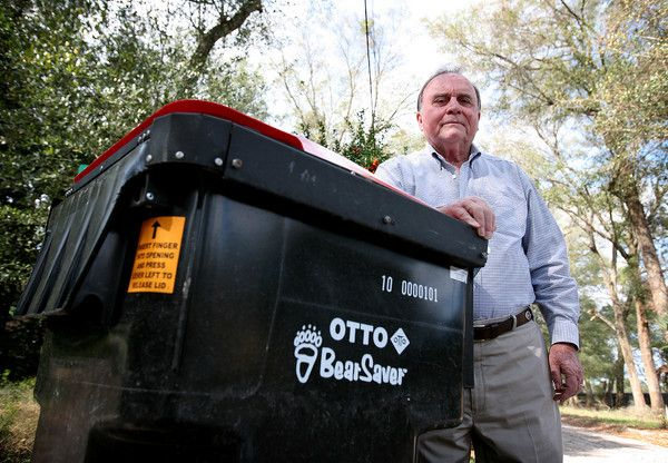 DeLand resident Martin Chandler stands with his bear-proof garbage can at his property on on February 16, 2012. He has several bears that live and frequent his property and also nests in one of his trees.