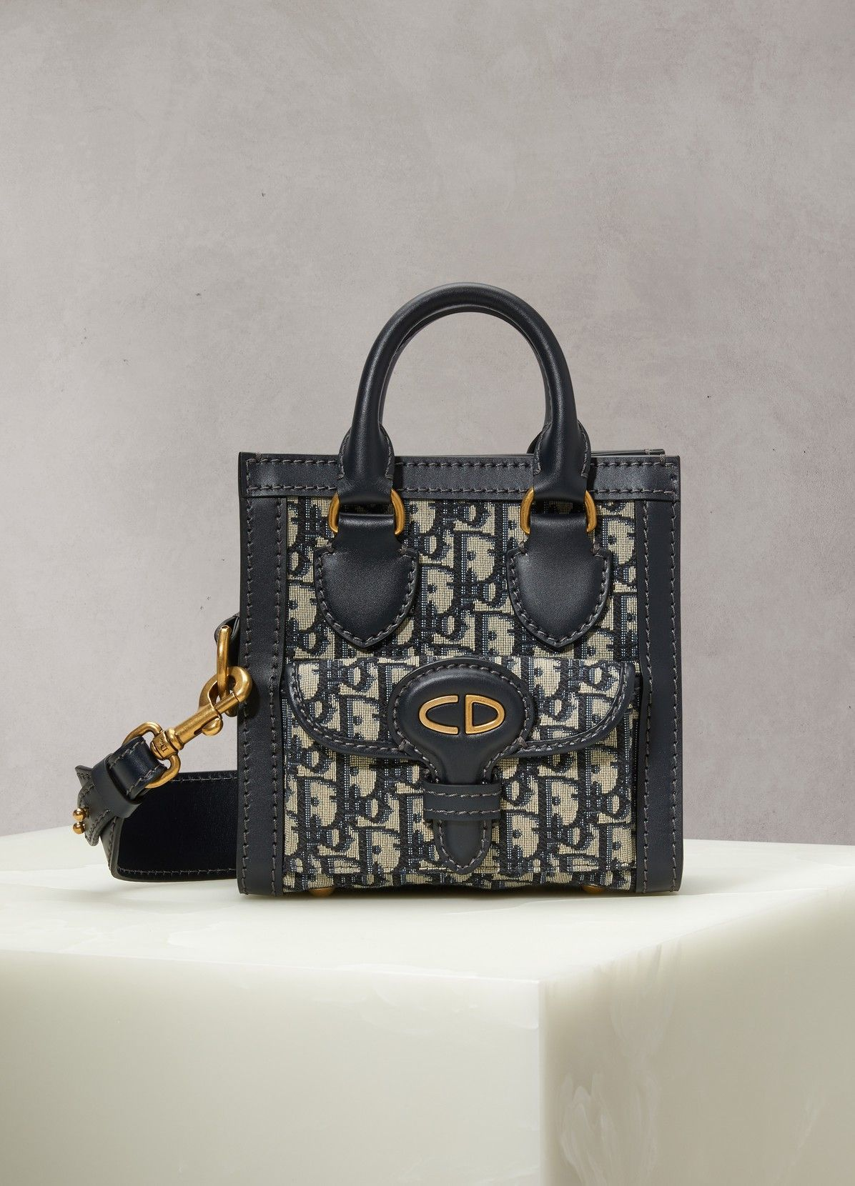 0940fe103b The Dior Oblique bag resembles a mini tote bag and is made from the  collection's signature fabric. Its calfskin leather details exemplify the  Parisian ...