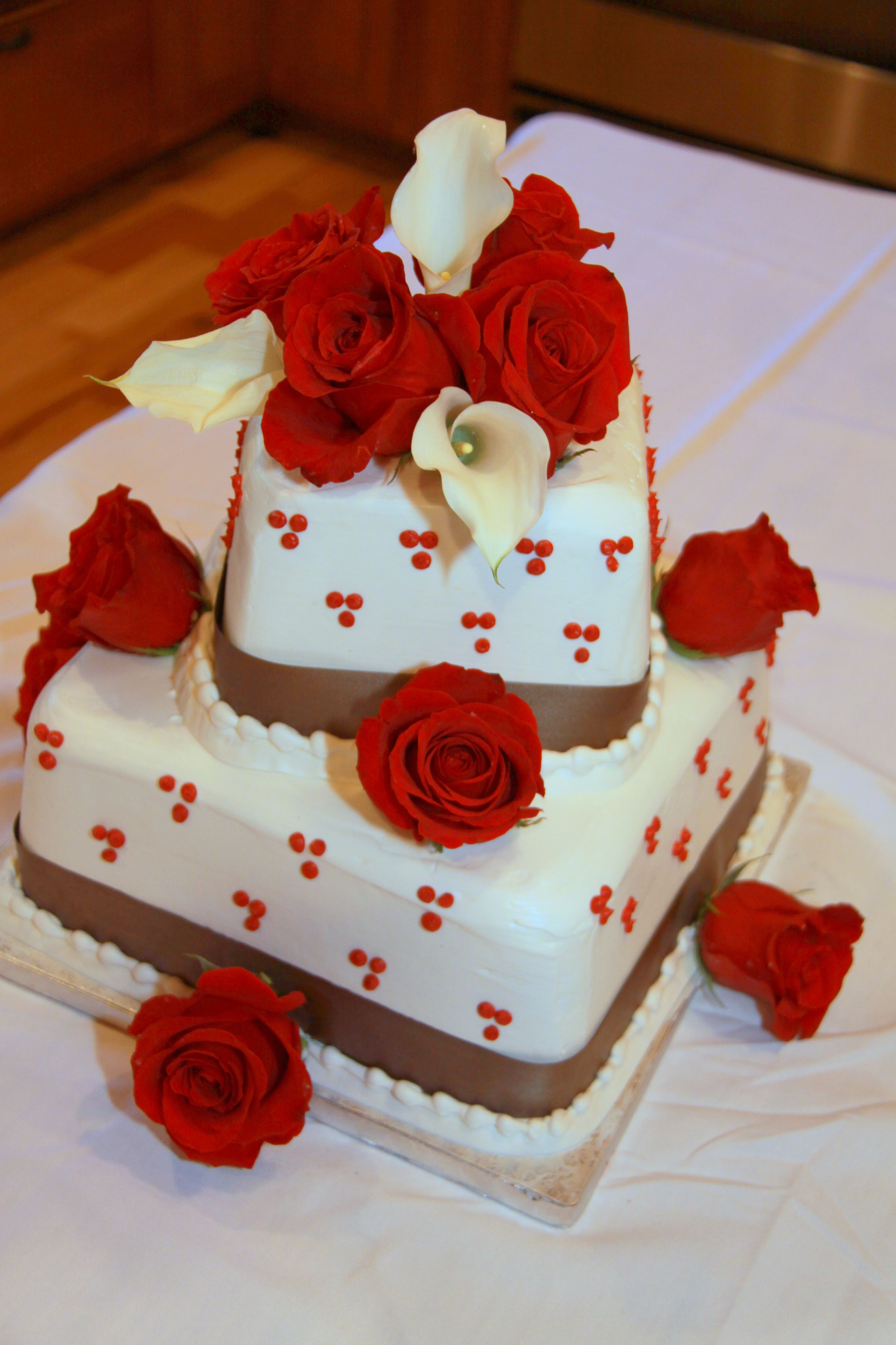 square, smooth iced wedding cake with fresh red roses