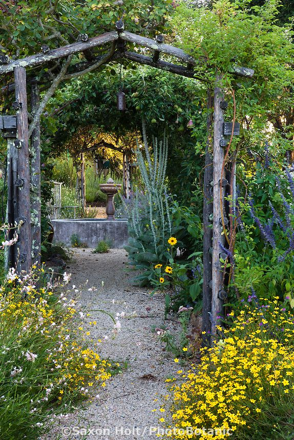gravel path lined with flowers through rustic country garden pergola to courtyard patiothe