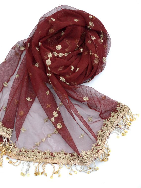 beautiful, deep red tulle shawl with gold embroidery and gold fringe.  This sheer scarf was created from vintage bridal sari. The edges have embroidered borders with gold metallic thread, sequins, and tiny beads. Light gold deigns with sequins are scattered across the rest of the scarf. Both short ends have gold fringe with sequins.  This embroidery is done with zari thread, which is a metallic, wound thread. Traditionally, the threads were gold, silver, and other precious metals. Zari means…
