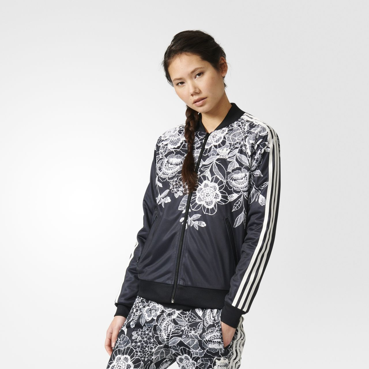 Sporty feminine style blends with a nature-inspired floral print in this women's track jacket. A collaboration with Brazilian label The FARM Company, this jacket combines the best of both worlds. A lace-like pattern of flowers covers you from shoulders to midriff, front and back. The white petals and tonal leaves on black have a vintage hand-stitched feeling, while 3-Stripes riding the sleeves makes it unmistakably adidas.