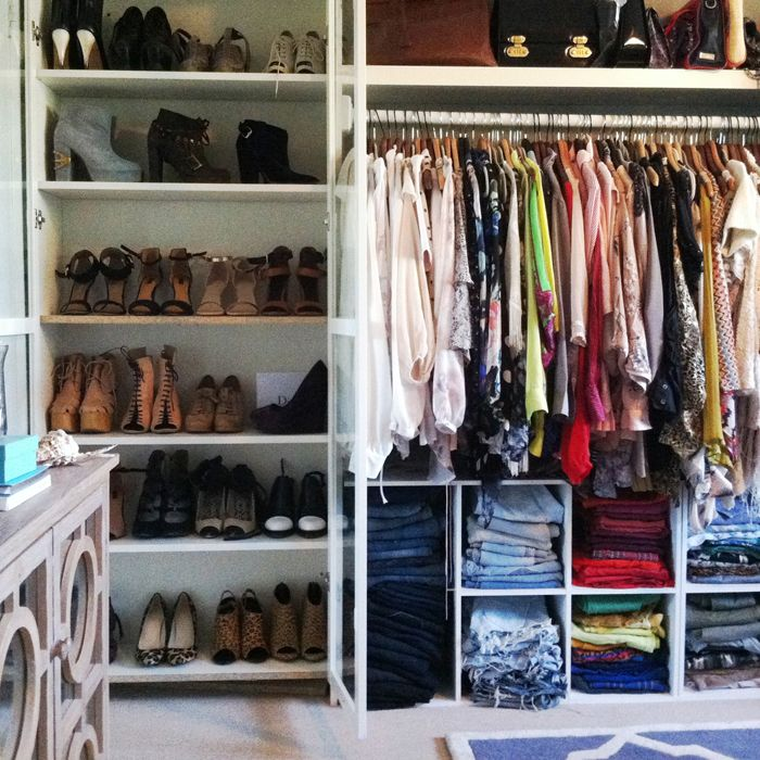 Bookshelf with glass doors for shoe storage, blocks on bottom for jeans and tanks. Ikea ideas.