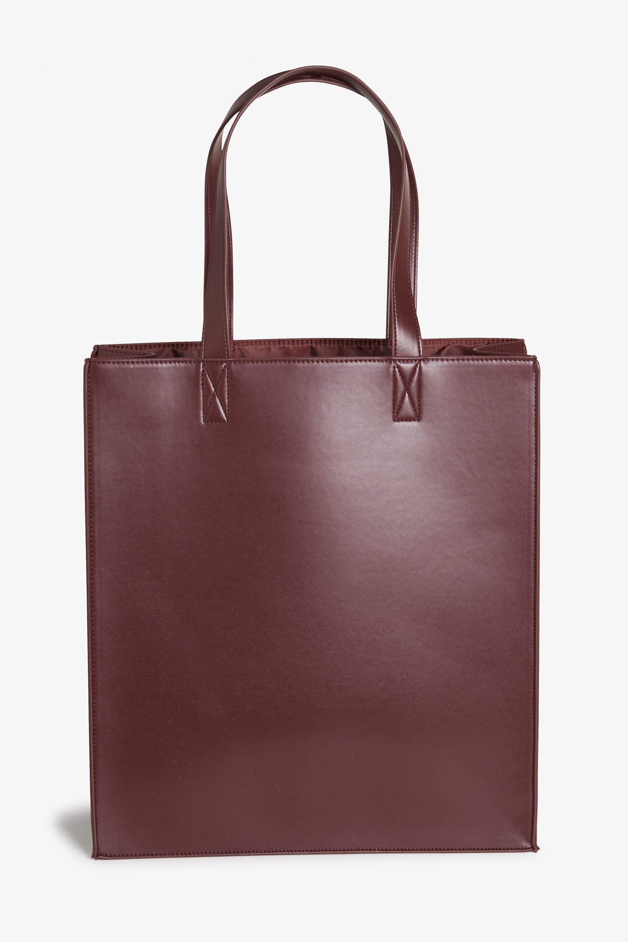 03d9da97f840a A minimalist faux leather tote bag. Single compartment with a pocket on the…