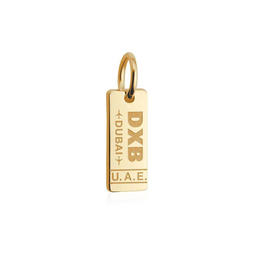 """Your 14k solid gold Mini Dubai Luggage Tag Charm features the IATA code for Dubai International Airport, DXB. Take home a timeless memento of the """"City of Surprises."""" Futuristic skyscrapers rising from desert sands, sub-zero ski fields beside an island shaped like a palm, tennis atop a hotel shaped like a billowing sail. Dubai will leave you wondering if it's all just a mirage… Approximate dimensions: 5.5 mm x 13.5 mm"""
