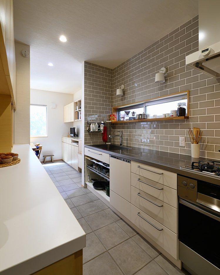 グレーの壁 床タイルのキッチン キッチンはステンレスシンク ステンレスカウンターで面材は白い革のようなテイストに グレーベースのインテリアなので 白のブラケット照明 白のレンジフード 白の面材がとても引き立ちます 最近はオープンなキッチンが増