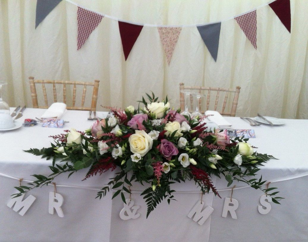 Vintage pinks and ivory in a long and low arrangement - beautiful match with the bunting!