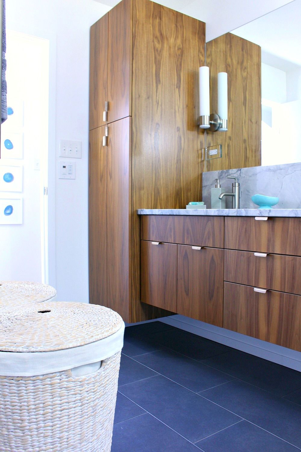 A Mid Century Modern Inspired Bathroom Renovation Before After Floating Walnut Vanity And Linen Tower Woven Hamper Charcoal Grey Floor