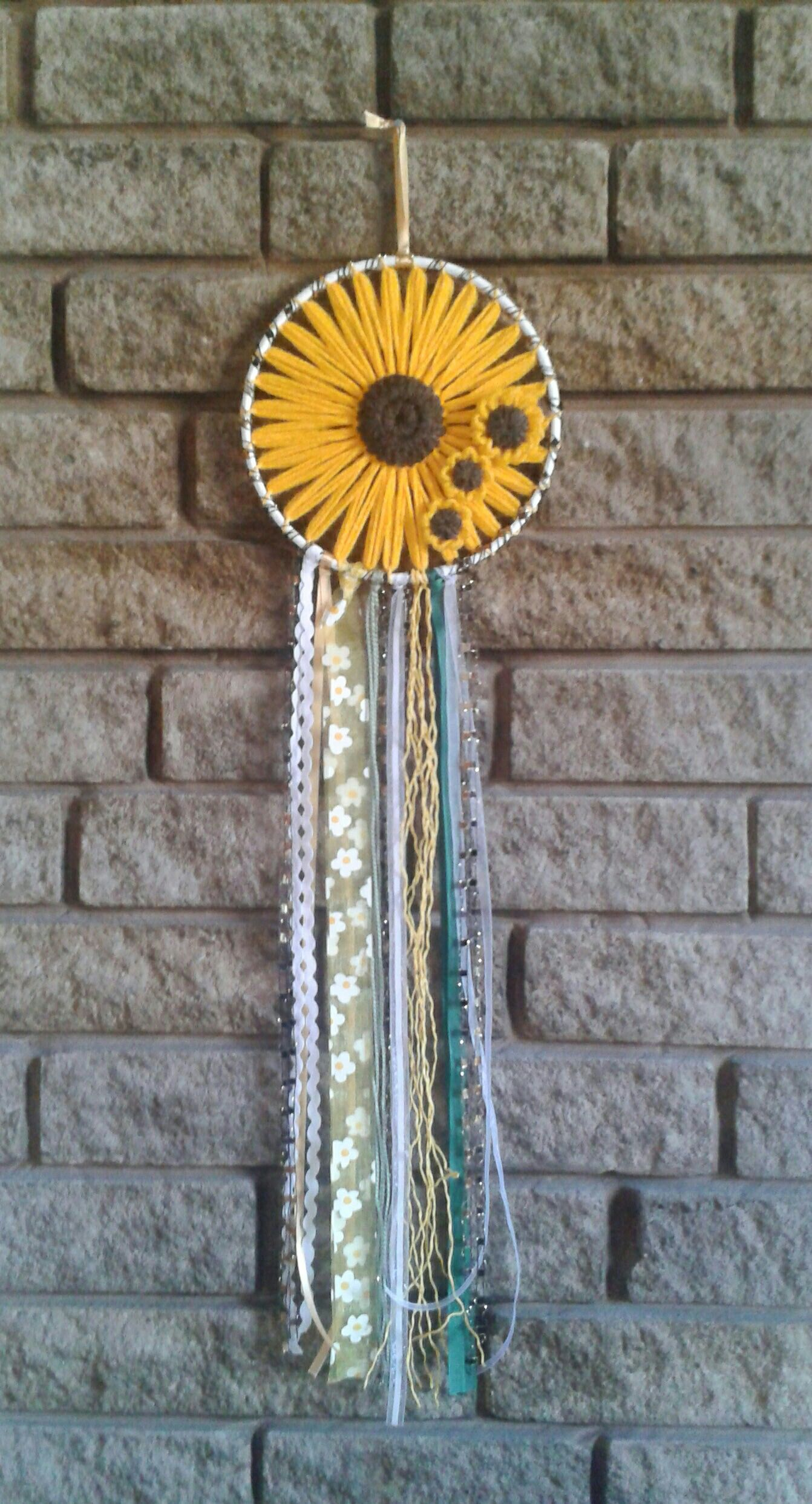 Gorgeous summer sunflower dreamcatcher. The centre of this 7 hoop is filled with a large loom knit sunflower & 3 smaller flowers  & finished with a variety of wool, raffia & ribbon streamers. Can be made to order in colours/size of your choice by contacting me via www.facebook.com/annepearsondesigns or www.instagram.com/annennepearsondesigns. This piece is available to buy at annepearsondesigns.tictail.com #sunflowerbedroomideas